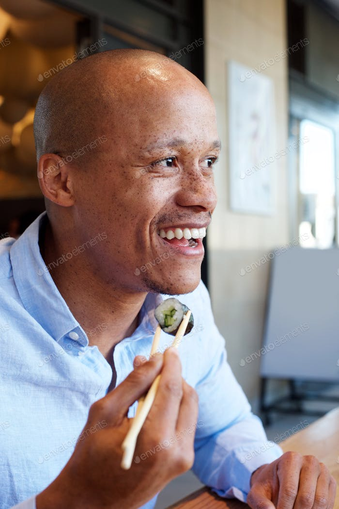 smiling african man enjoying eating sushi