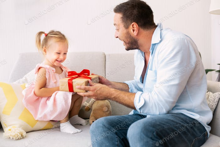 Cheerful father congratulating his cute little girl