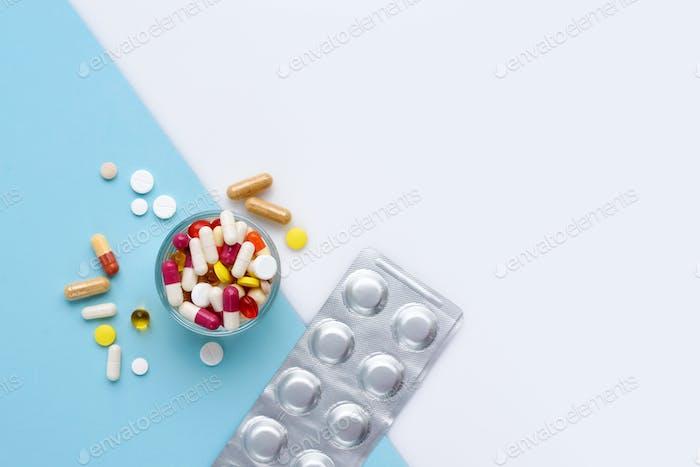 Ein Glas voller Pillen, Tabletten, Kapseln auf blauem und weißem Hintergrund