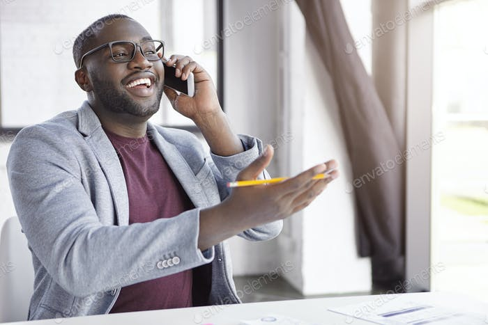 Positive African American male enterpreneur dressed in formal clothes, has conversation over smart p