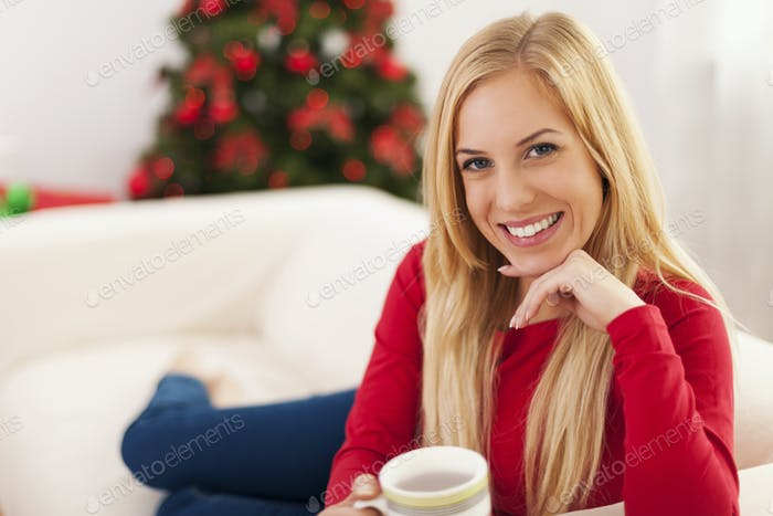 Beautiful blonde woman relaxing on the sofa in christmas time