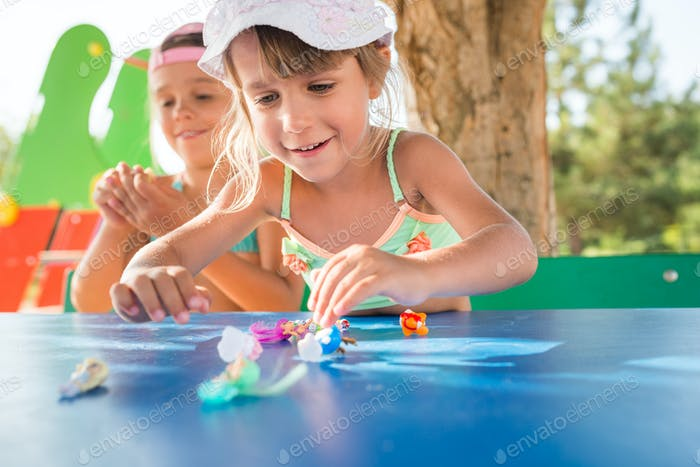 Two little cute girls playing dolls outdoors