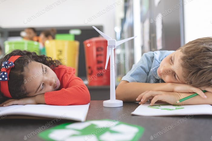 Tired school kids observing windmill mockup between them in classroom