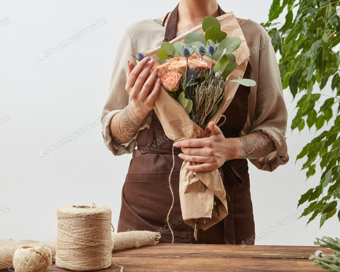 Woman florist with fresh beautiful handmade bouquet from fesh fragrant flowers ang green leaves on a