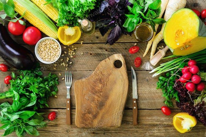 Gemüse auf hölzernem Hintergrund. Kräuter, Basilikum, Zwiebel, Kürbis, Pinienkerne, Tomaten, Mais, Rettich