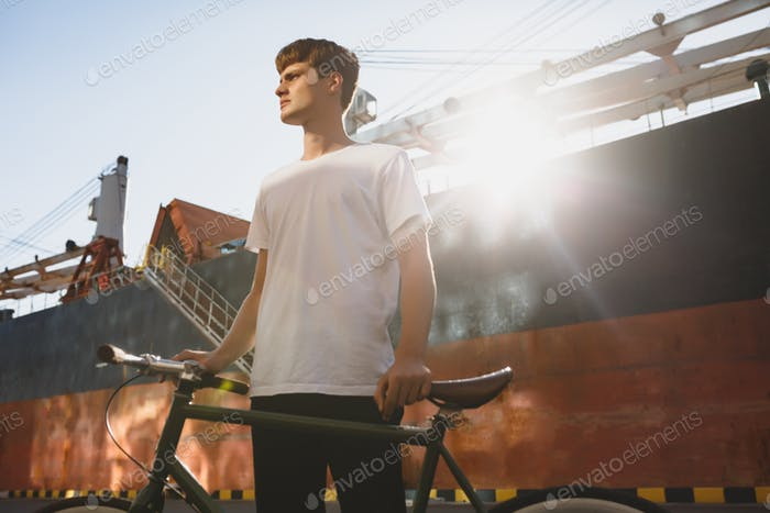 Young man in white t-shirt standing and posing on camera with big ship on background