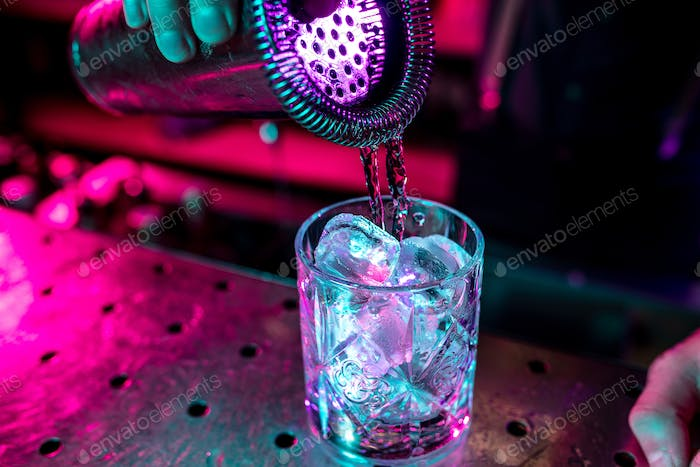 Close up of alcoholic cocktail, beverage, drink, glass full of ice in multicolored neon light