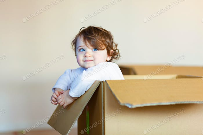 Toddler baby girl sitting inside brown cardboard box.