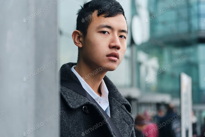 Portrait of young Asian businessman confidently looking in camera