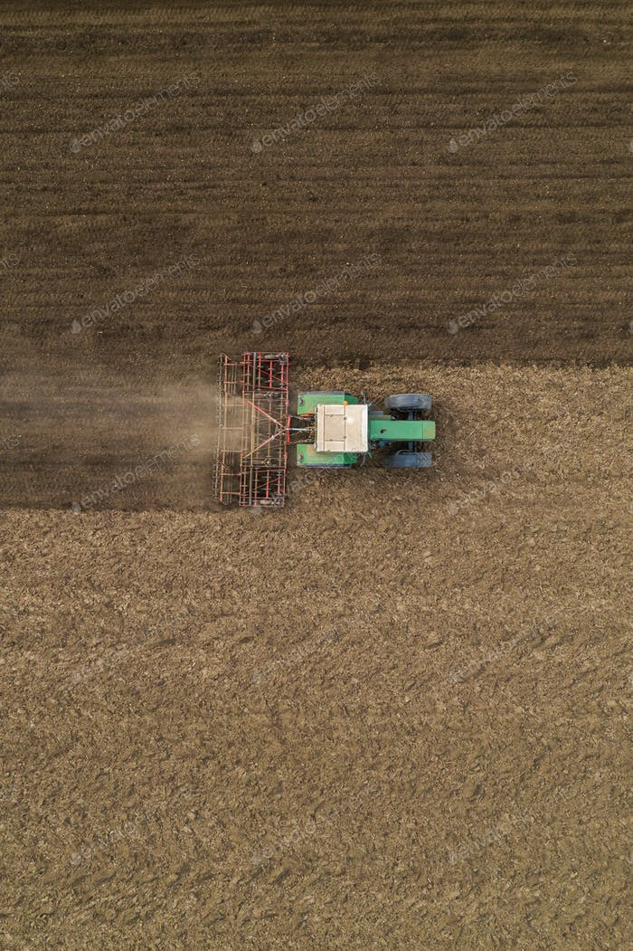 Vista aérea de la labranza de tractores agrícolas y el desgarrador campo arado, directamente por encima de los aviones no tripulados