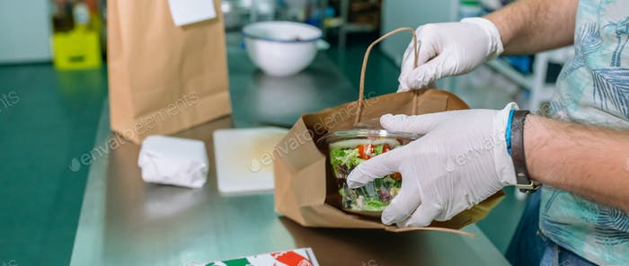 Unrecognizable cook packing a takeaway order