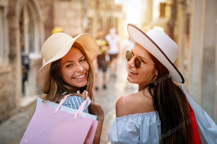 Sale, consumerism, shopping and people concept. Happy young women with shopping bag
