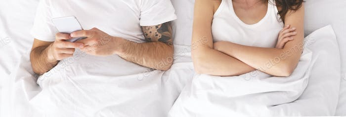 Man ignoring his offended wife in bed, playing video game