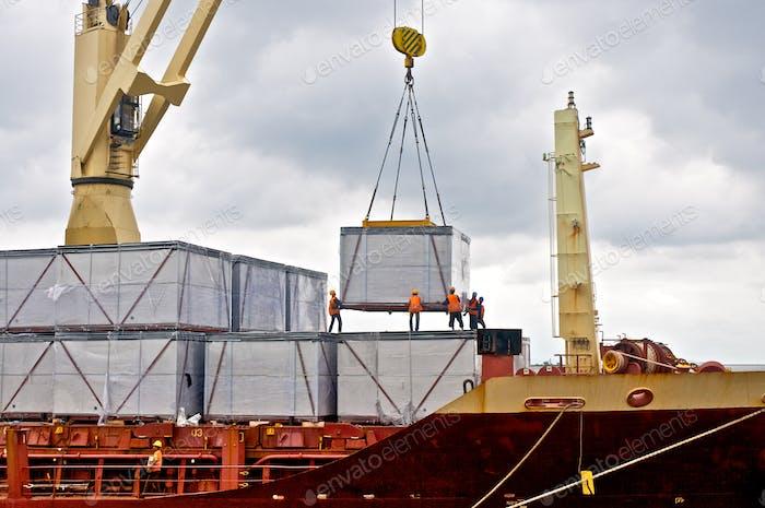Loading cargo into the ship in port shipyard