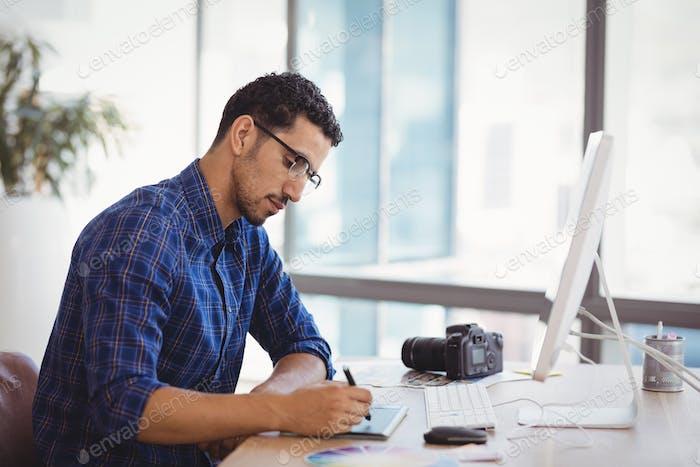 Graphic designer using graphic tablet at desk