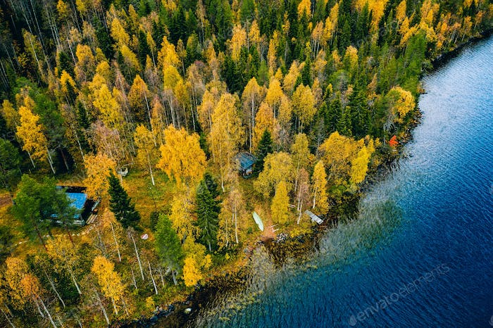 Aerial view of cottage in autumn colors forest by blue lake in rural Finland