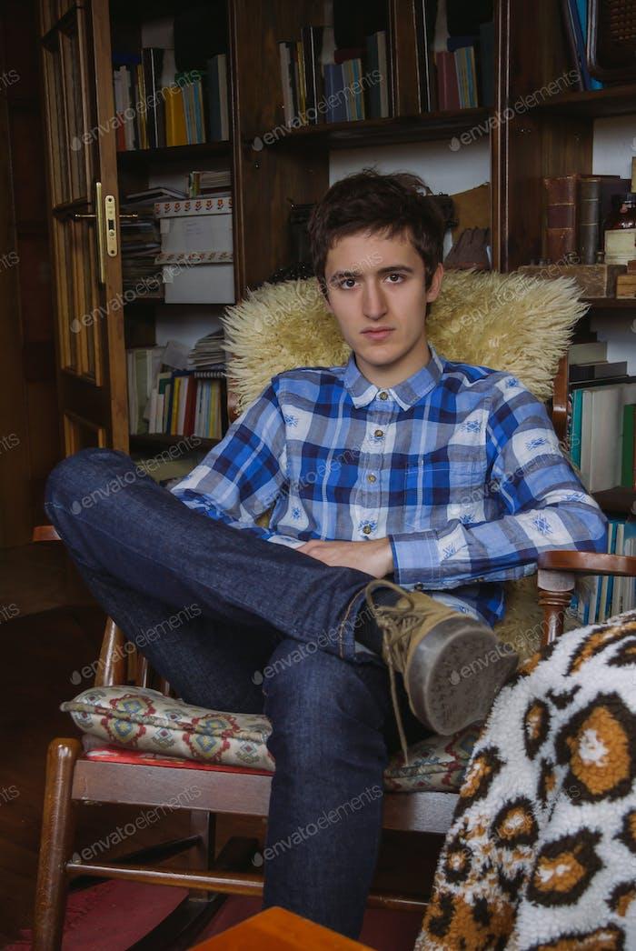 Junger Mann mit kariertem Hemd und Jeans sitzt auf einem Schaukelstuhl