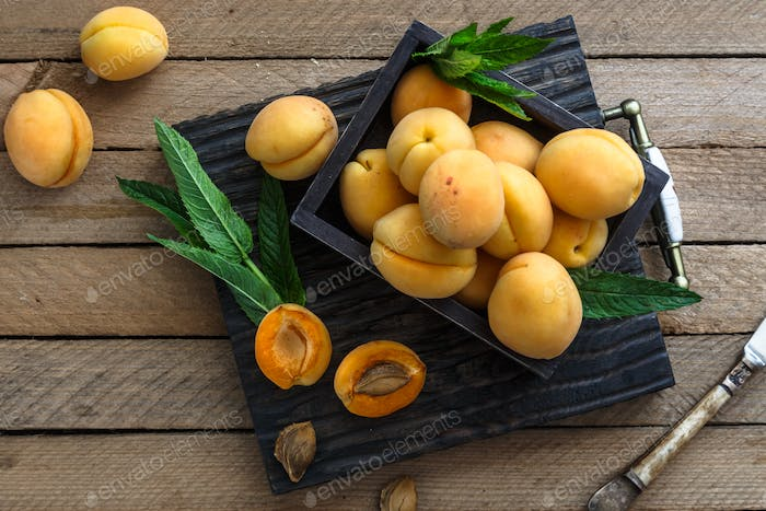 Apricots on wooden board, top view