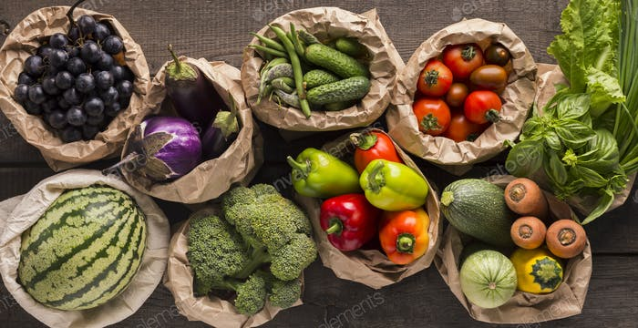 Eco vegetables and fruits in cotton bags on floor background