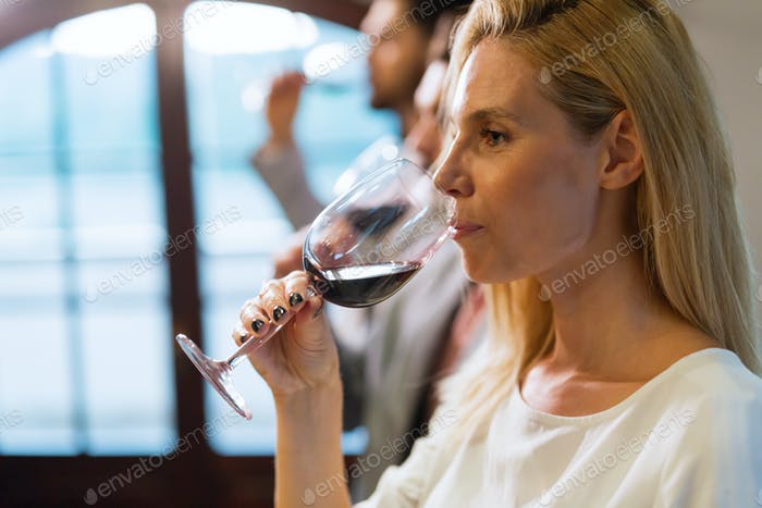 Beautiful blonde woman drinking glass of red wine