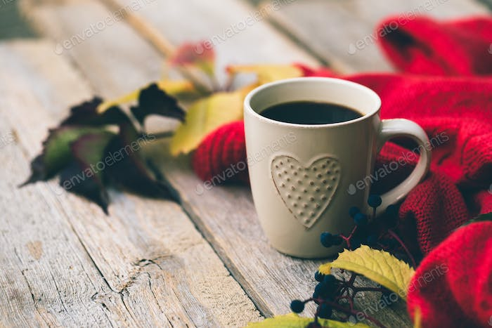 Mug of hot coffee in autumn setting on a wooden table with a knitted scarf, sweater.