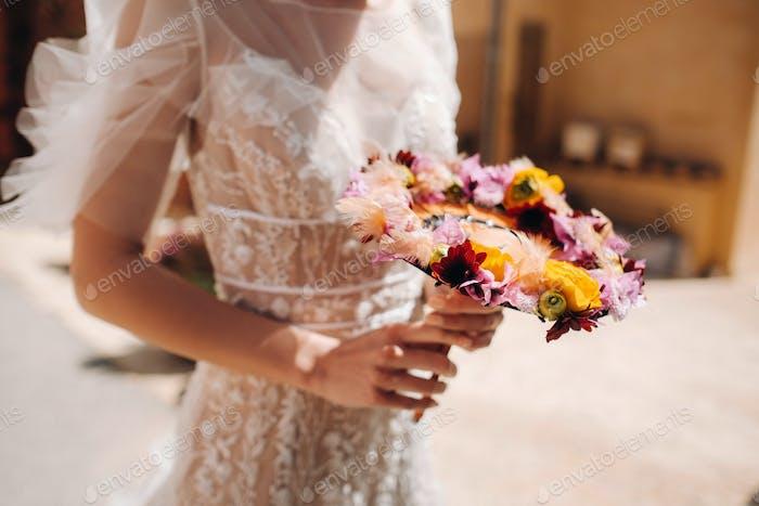 eine Braut in einem Hochzeitskleid mit einem kreativen Blumenstrauß Nahaufnahme. ungewöhnlicher Blumenstrauß in den Händen der