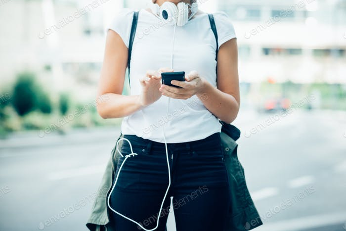 From the neck down view of young woman holding a smart phone tap