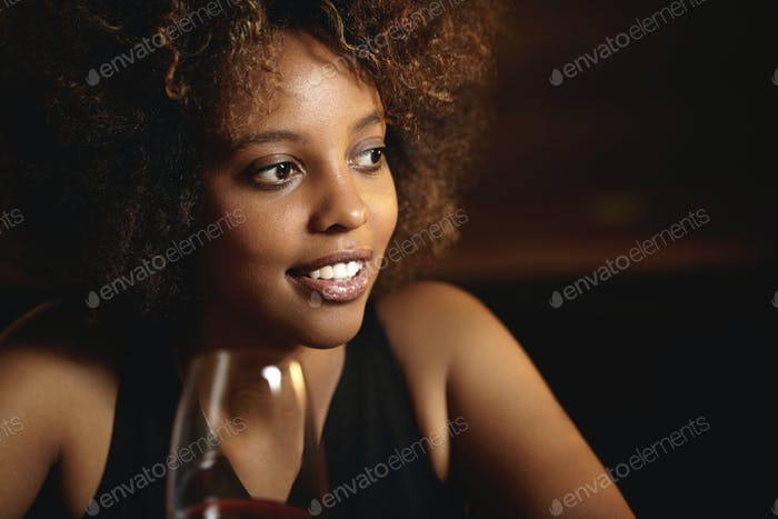 People and leisure. Elegant African woman with perfect tanned skin sitting at restaurant, holding gl