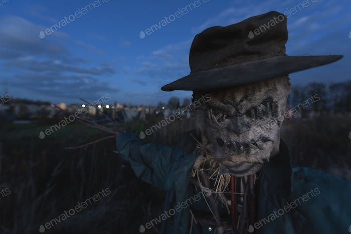 Terrible scarecrow in dark cloak and dirty hat stands alone on a cemetery