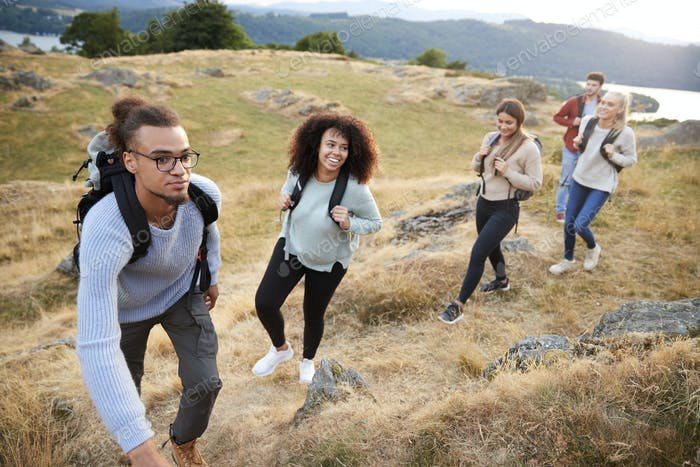 A multi ethnic group  of five young adult friends smile while climbing