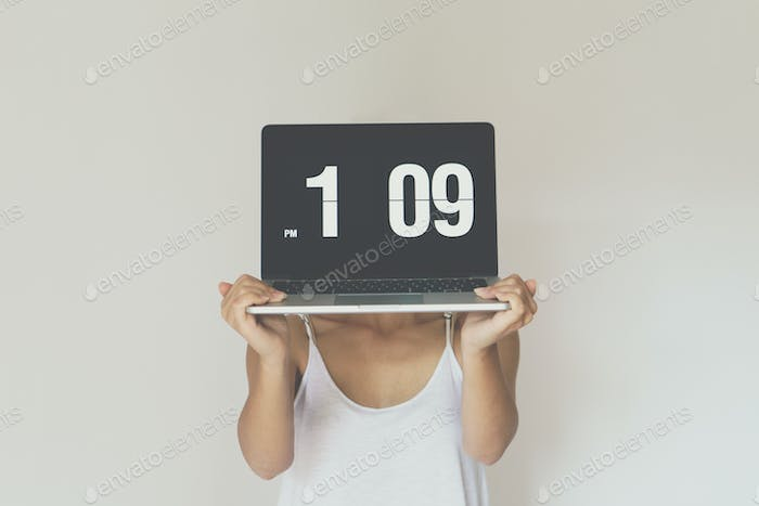 Woman holding computer with clock front of her face.