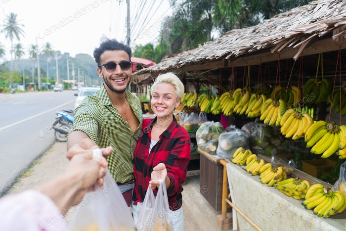 Couple Buying Bananas On Street Traditional Market, Young Man And Woman Travelers