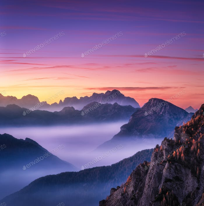 Mountains in fog at beautiful sunset in autumn in Dolomites