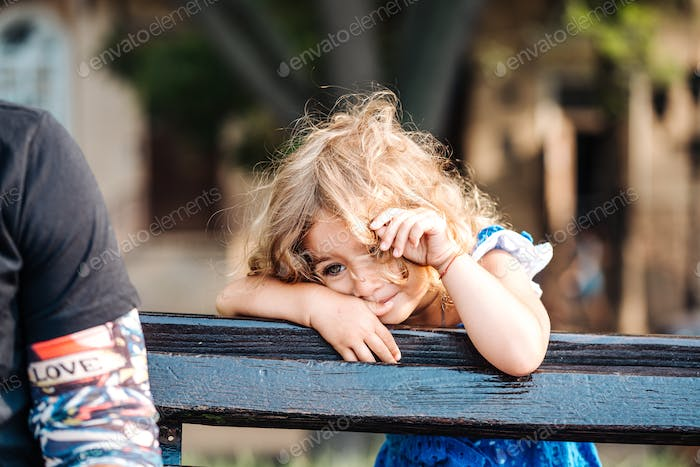toddler girl standing behind a bench