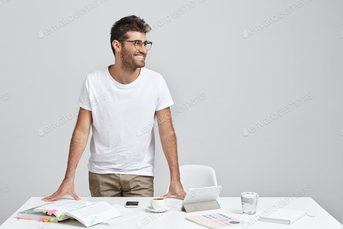 Unshaven positive young male teacher in glasses and casual clothes standing at desk in classroom and
