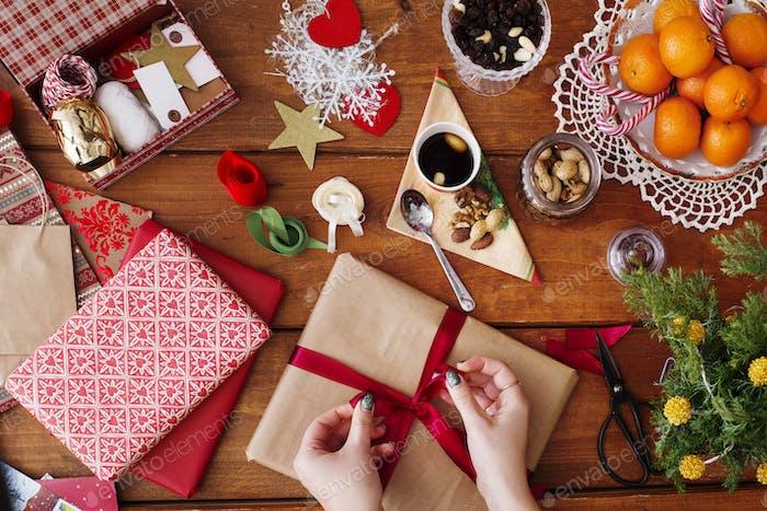 Abgeschnittenes Bild der Hände binden Bogen auf Weihnachtsgeschenk auf Holztisch