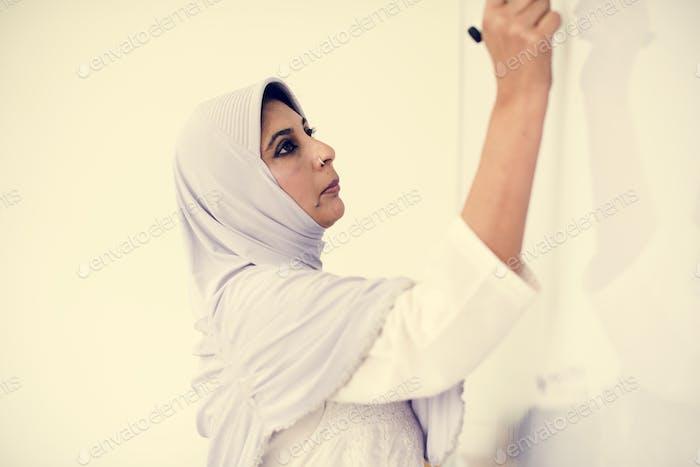 A Muslim teacher writing on a white board