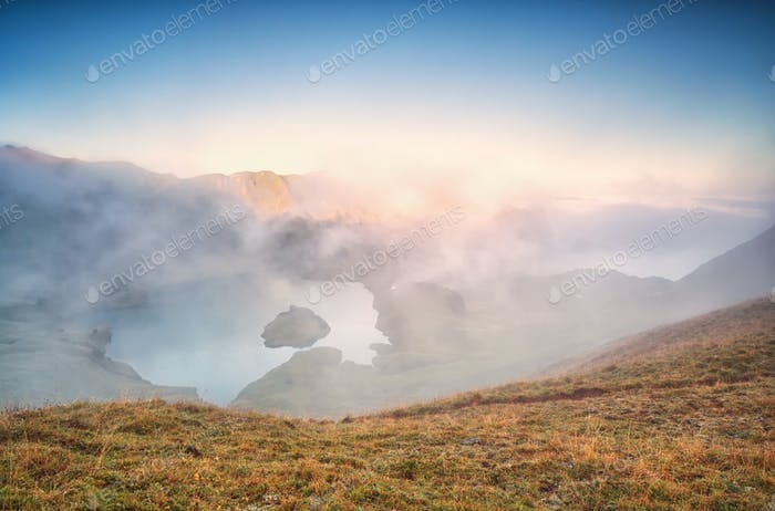 fog over alpine lake at sunrise