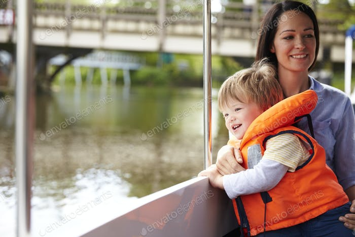 Mother And Son Enjoying Day Out In Boat On River Together