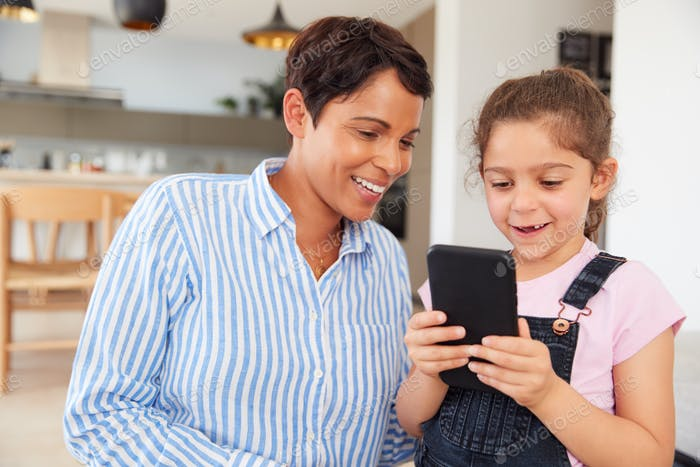 Mother And Daughter Looking At Mobile Phone Together At Home