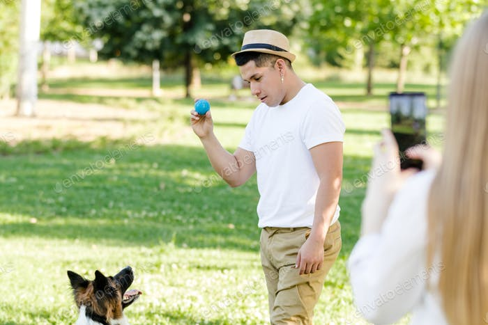 Young latino man playing and training with his border collie dog while his girlfriend takes a