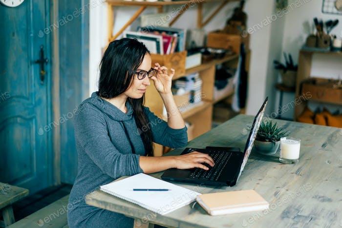 Intelligentes Geschäft erfolgreiche herrische Frau am Tisch liest in einem Laptop. Von zu Hause aus arbeiten