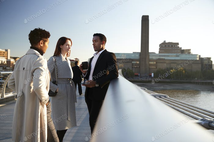 Side view of three millennial business colleagues stand talking on Millennium Bridge