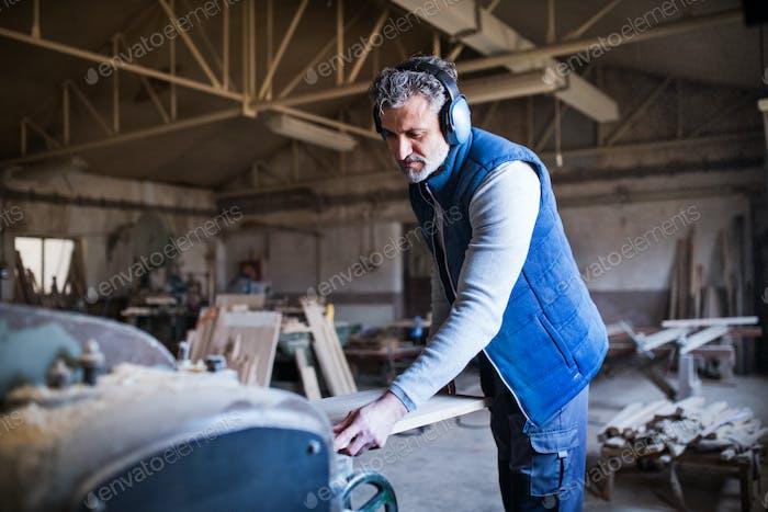 Ein Mann Arbeiter in der Tischlerei, arbeitet mit Holz.