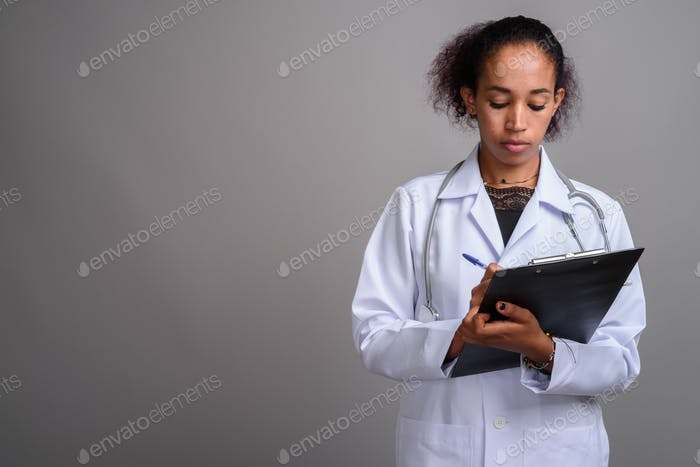 Young beautiful African woman doctor against gray background