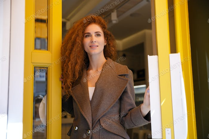 Young red haired woman leaving cafe