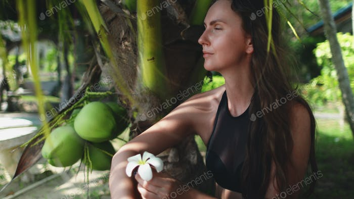 young carefree woman sitting under palm tree leaf