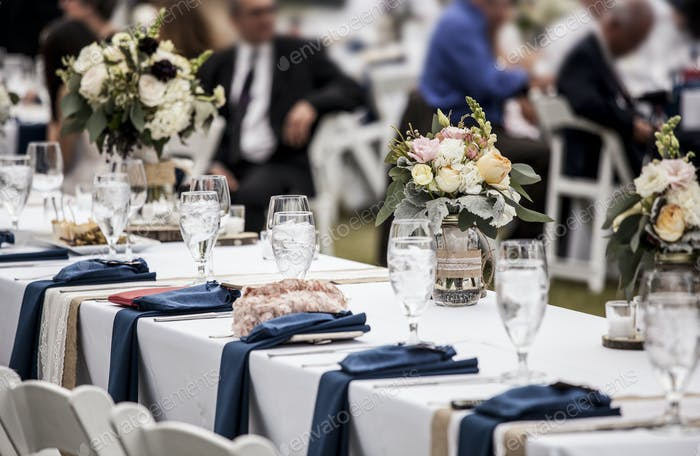 Table set up for wedding reception with people out of focus in b
