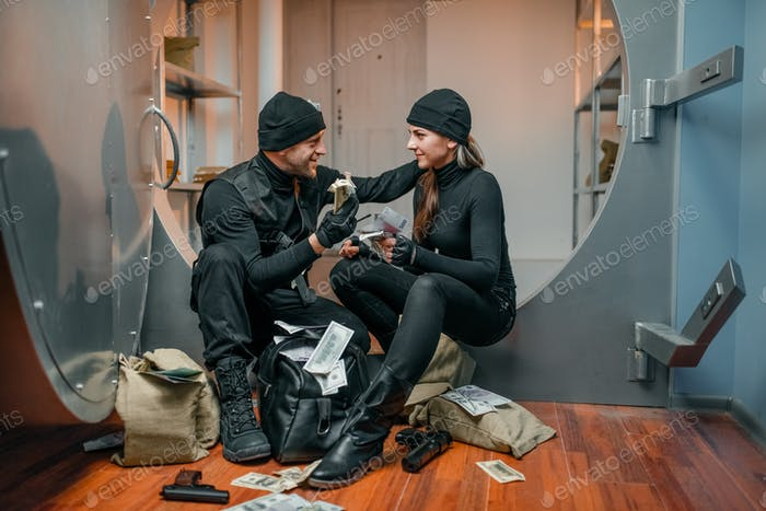 Two robbers in black uniform stuff bags with money