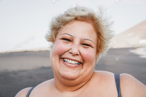 Portrait of curvy woman smiling on camera wearing bikini with beach in background - Focus on face